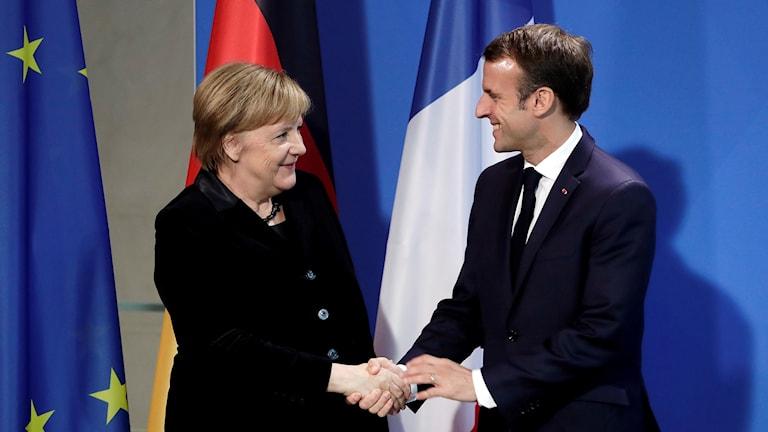 Tysklands förbundskansler Angela Merkel skakar hand med Frankrikes president Manuel Macron.
