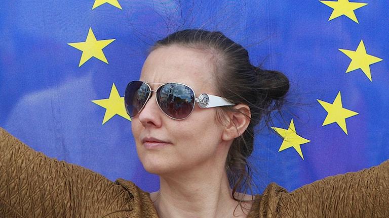 En kvinna står framför EU-flagga.