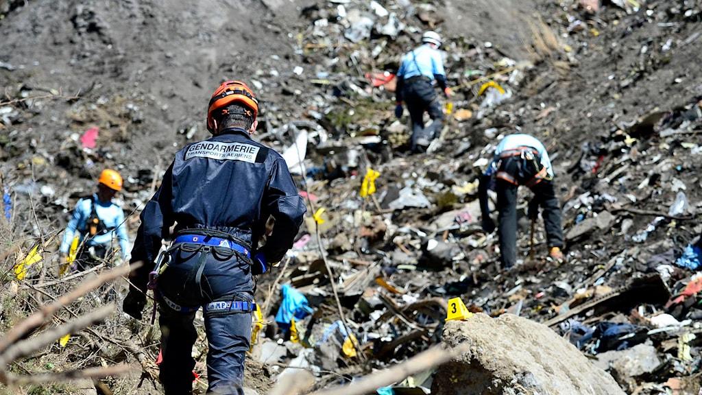 Fyra personer som tittar på marken vid nedslagsplatsen.