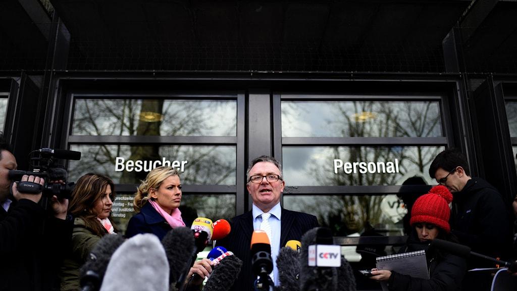 Enman står vid en glasdörr omringad av journalister och fotografer.