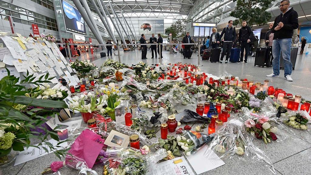 Blommor och ljus på Düsseldorfs flygplats. Foto: Martin Meissner/TT.