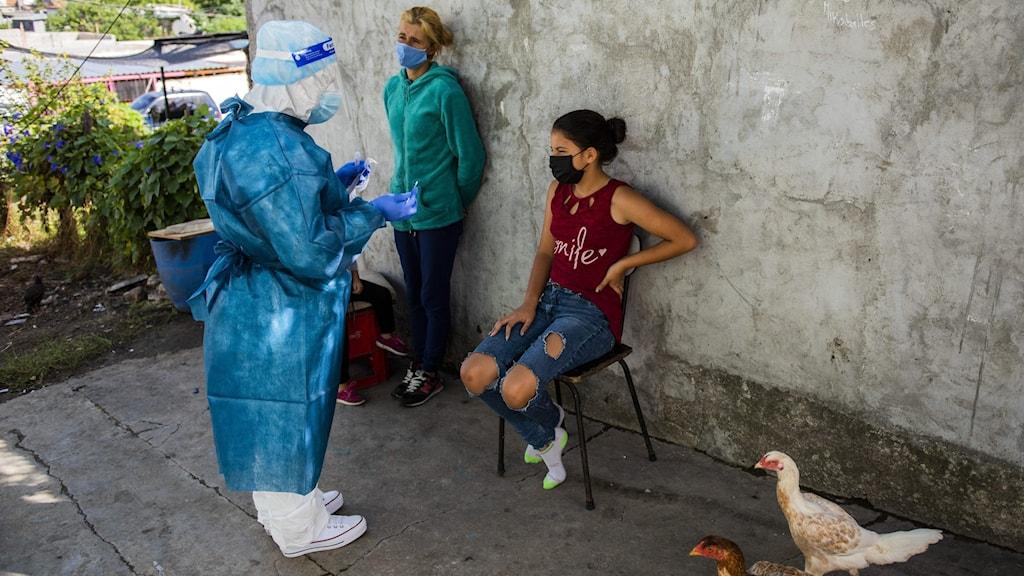 kvinna i skyddsdräkt ska testa ung tjej på stol