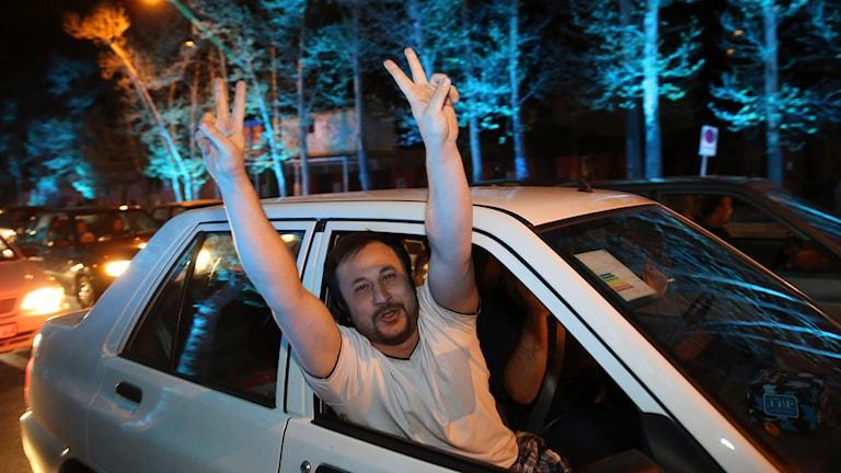 En iransk man visar segertecken efter beskedet om ramavtalet på en gata i norra Teheran. Foto: Vahid Salemi/TT.