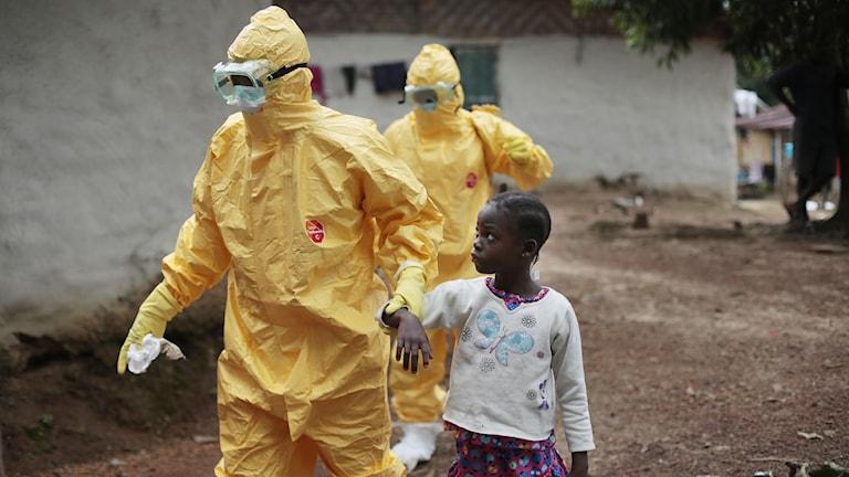 Arkivbild: Sjukvårdspersonal i skyddskläder hjälper liten flicka.