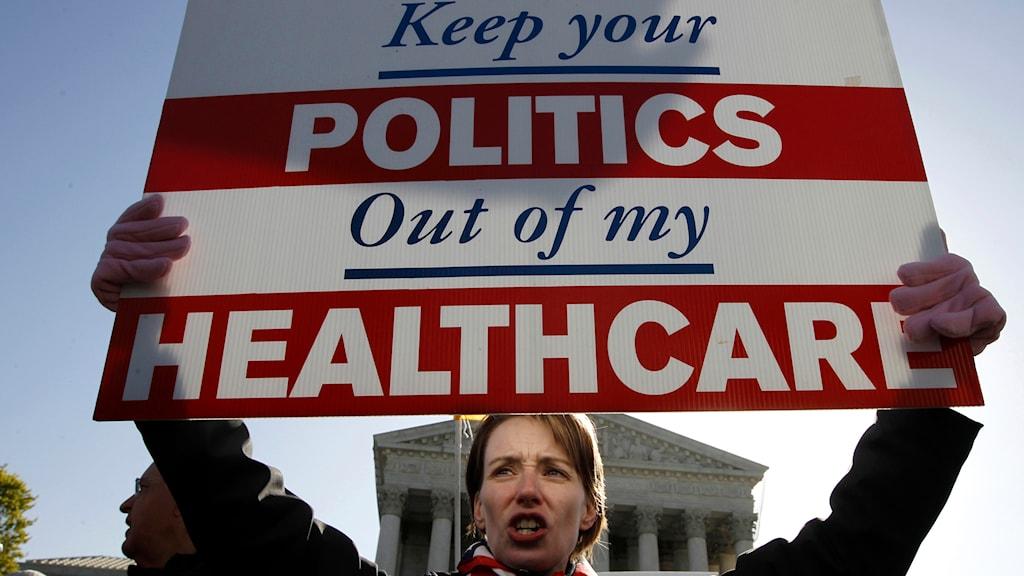 Kvinna håller upp rödvitt plakat med protesttext mot Obamacare