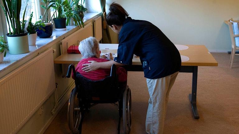 En undersköterska hjälper en äldre person som sitter i rullstol vid ett matbord på ett äldreboende. Foto: Henrik Montgomery/TT.