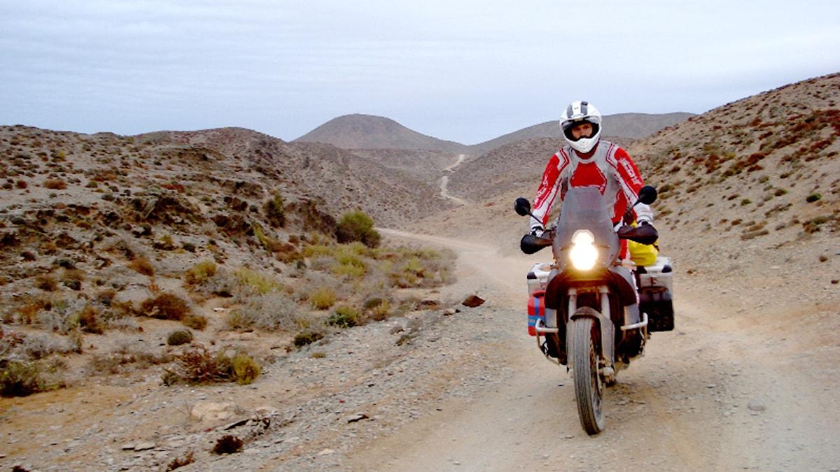 Man klädd i rött på motorcykel i torr och kuperad terräng. Foto: Privat