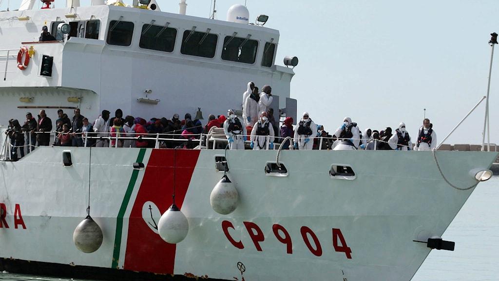 Räddade migranter väntar på att få kliva av kustbevakningens fartyg i södra Italien. Foto: Francesco Malavolta/TT.