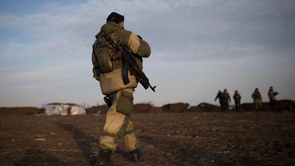 Beväpnad man på ett fält i Ukraina. Foto: Evgeniy Maloletka/TT.