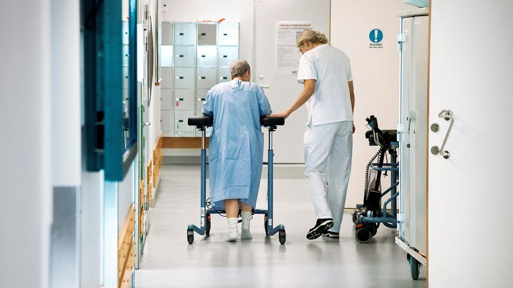 En patient går med hjälp av en gåstol i en sjukhuskorridor. Patienten får assistens av en sjuksköterska.
