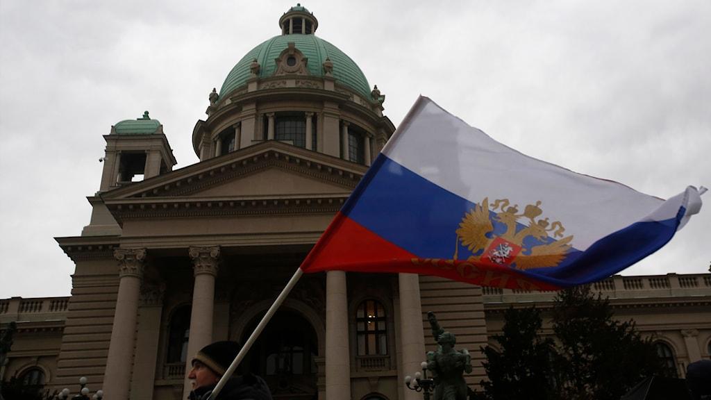 En man håller den ryska flaggan i en protest mot Nato framför det serbiska parlamentet för några veckor sedan. Foto: Darko Vojinovic/TT.