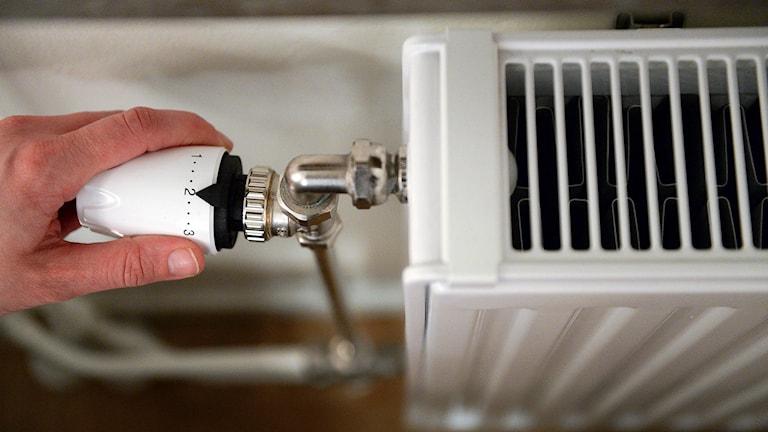 En hand som håller i reglaget som justerar värmen på ett element.
