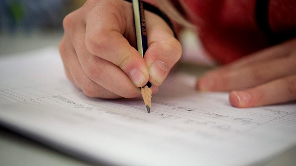 En lågstadieelev i årskurs 2 i Sofia skola skriver på ett papper med en penna Foto: Jessica Gow / TT