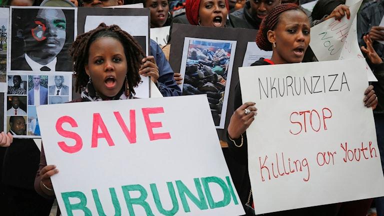 """Demonstranter som håller upp plakat med texten """"rädda Burundi""""."""