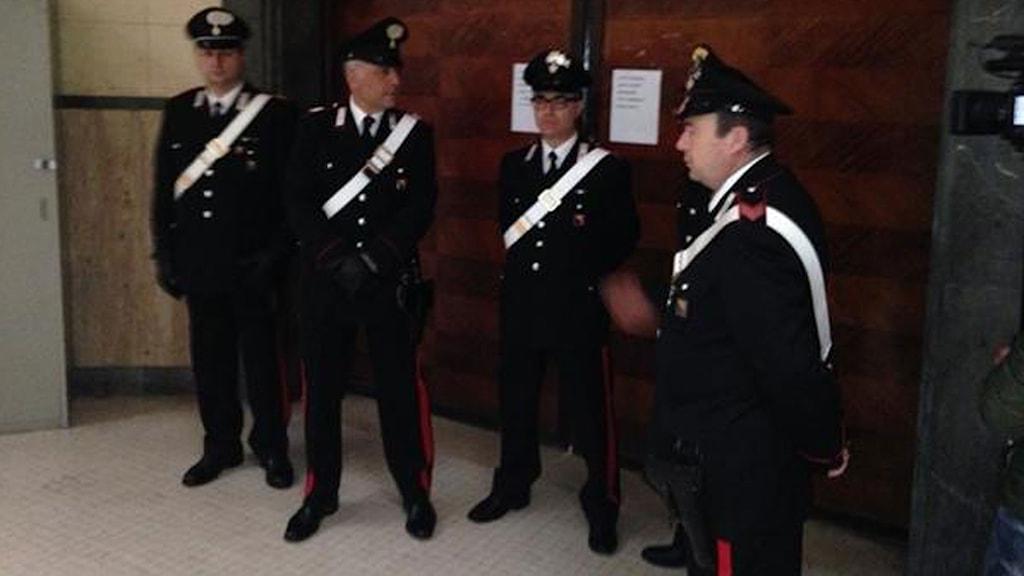 Fyra vakter utanför de stängda dörrarna där häktningsförhandlignen pågår.