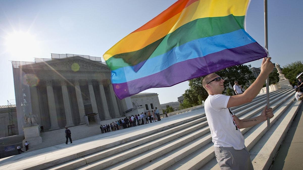 En gay-aktivist håller upp en regnbågsflagga utanför Högsta domstolens byggnad i Washington DC. Foto: Scott Applewhite/TT.