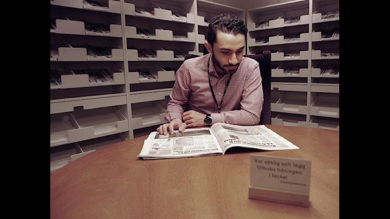 Vänsterpartisten Daniel Riazat läser en tidning i riksdagshuset i Stockholm