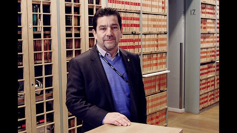 Miljöpartisten Marco Venegas står i riksdagshusets bibliotek