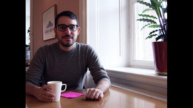 Folkpartisten Robert Hannah sitter med en mugg kaffe i riksdagshusets cafeteria