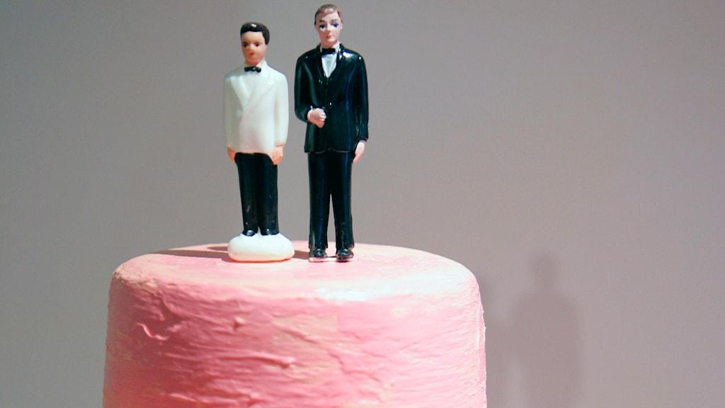 Två figurer av två välklädda män som ska gifta sig på en tårta.
