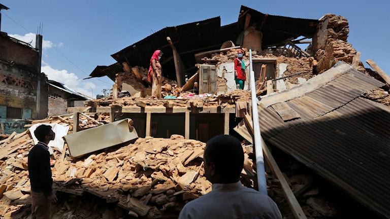 En nepalesisk familj står i sitt raserade hus i byn Shautarra. Foto: Manish Swarup/TT.