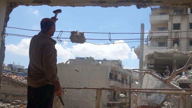 En man håller i en hacka, står i ett hus som är sönder.