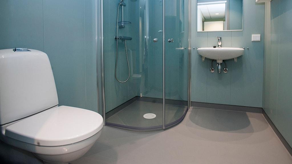 Ett badrum med toalett, duschkabin och handfat.