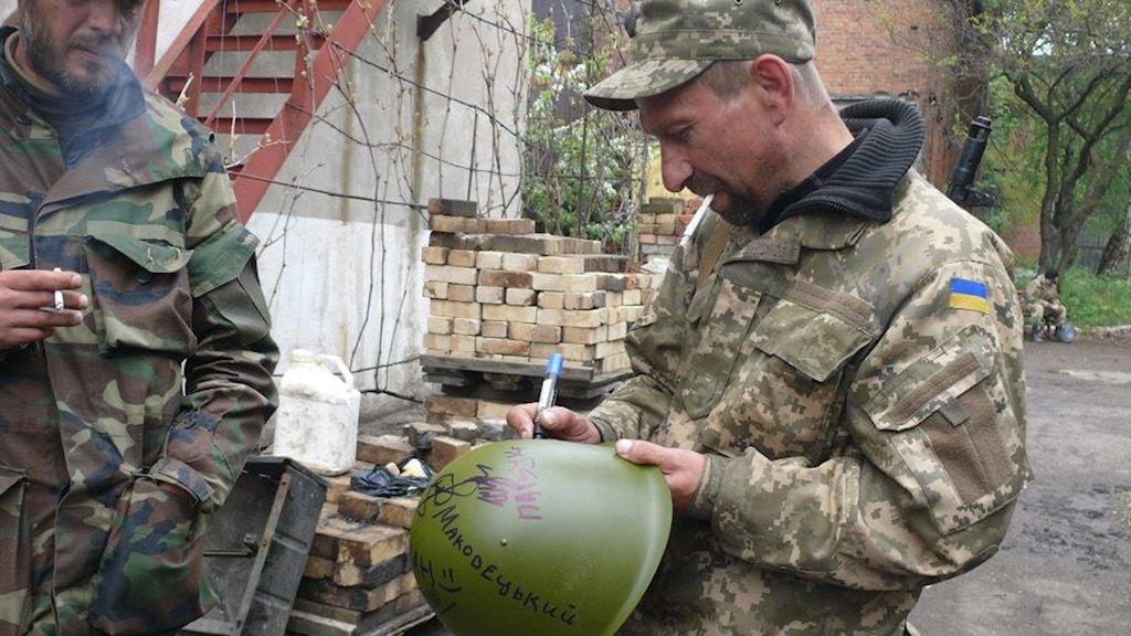 Hjälmar med soldaternas underskrifter ska auktioneras ut av volontärer i Kiev för att få in mer pengar till soldater och flyktingar. Foto: Maria  Persson Löfgren/Sveriges Radio.
