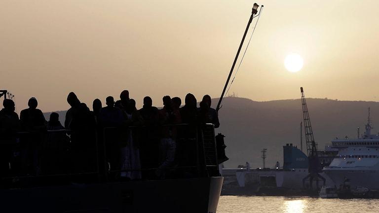 Migranter som flytt över Medelhavet väntar på att få gå iland på Sicilien. Foto: Antonio Calanni/TT.
