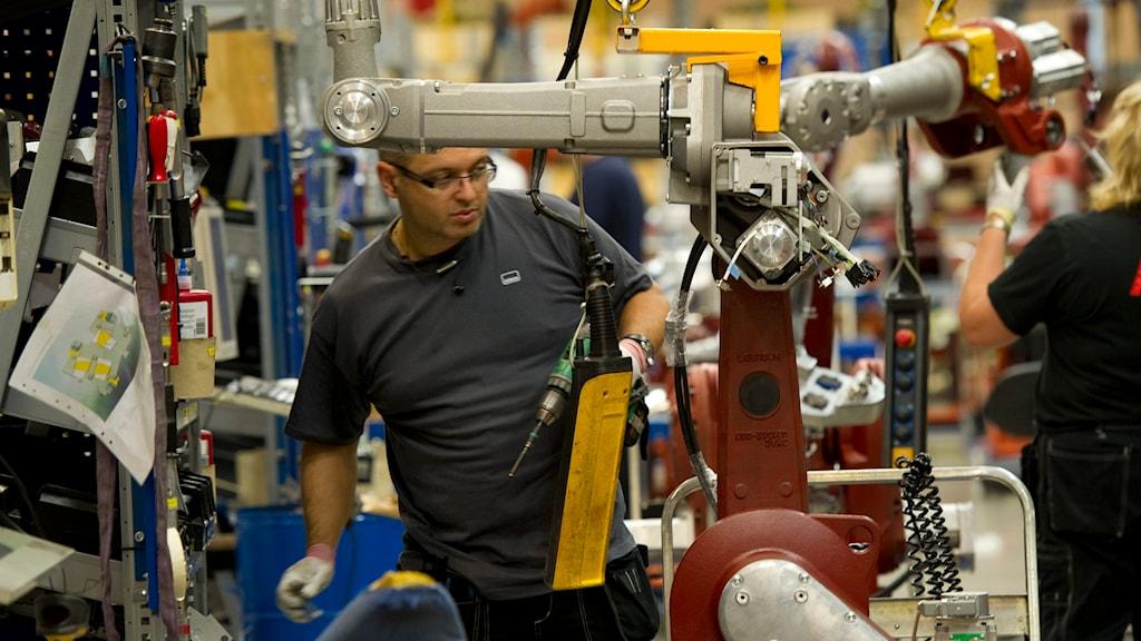 Vekrstadsarbetare i grå tröja jobbar vid en robotmaskin