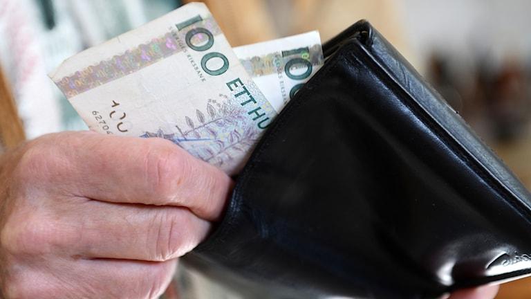 En man stoppar ner två hundralappar i sin plånbok. Foto: Fredrik Sandberg/TT.