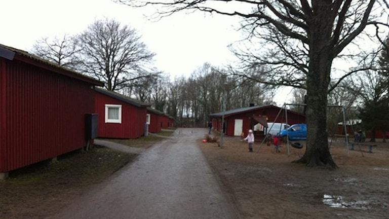 Röda campingstugor och barn som leker. Bilden är tagen på Lundegårds camping på Öland.