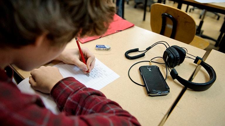 Högstadieelev skriver på papper. Foto: Jessica Gow/TT.