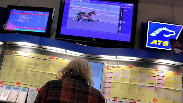 Man med nacke mot kameran står och tittat på lopplistor och TV-skärmar i ATG-butik