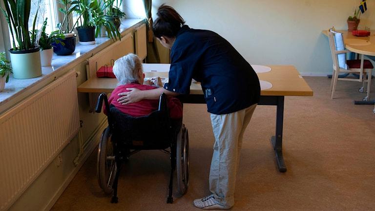 En anställd hjälper en kvinna som i en rullstol vid ett bord på ett äldreboende.  Foto: Henrik Montgomery/TT.