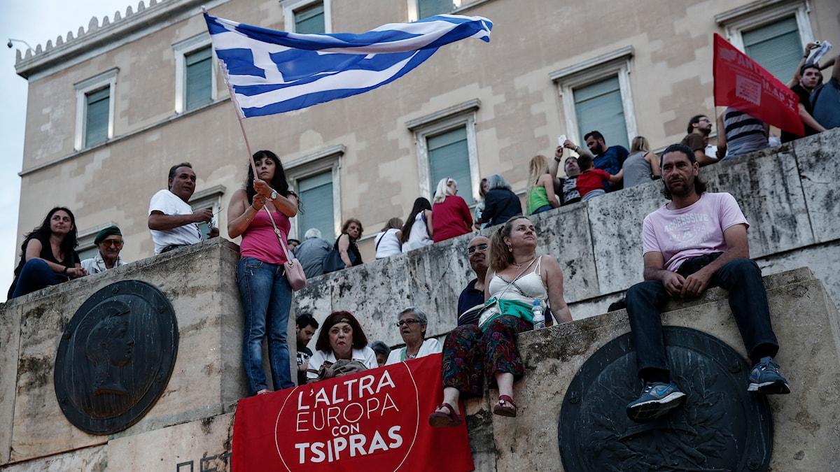 En person håller i en grekisk flagga omringad av andra människor.