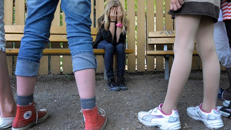En ensam flicka på en skolgård sitter med händerna för ansiktet medan en grupp flickor tittar på. Foto: Janerik Henriksson/TT.