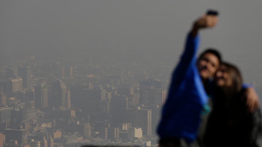 Par tar en bild på sig själva framför Santiago som är täckt av föroreningar. Foto: Jorge Saenz/TT.