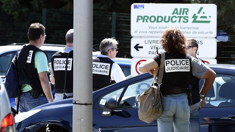 Poliser står vid bilar.