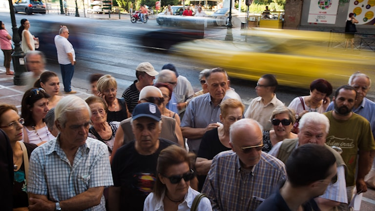 Pensionärer väntar utanför nationalbanken i Aten.