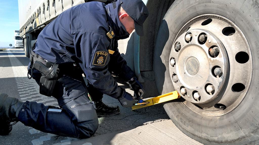 En polis klampar en lastbil i Malmö. Foto: Erland Vinberg / TT.