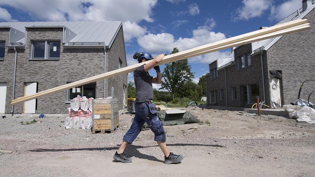 snickare med plankor vid husbygge