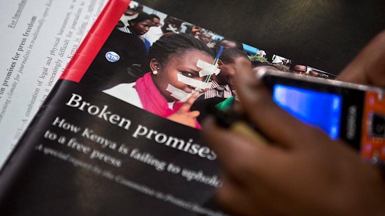 En journalist håller i en kopia av CPJ:s rapport om pressfriheten i Kenya. Foto: Ben Curtis/AP/TT.