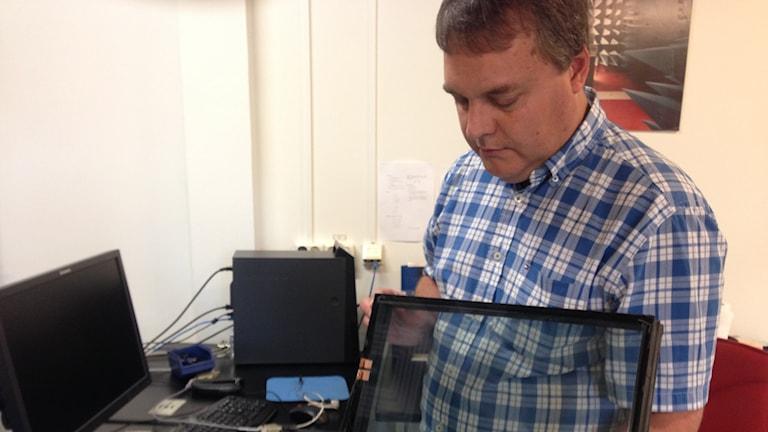 Jan Carlsson visar upp en prototyp på ett fönster som förstärker mobilsignaler.