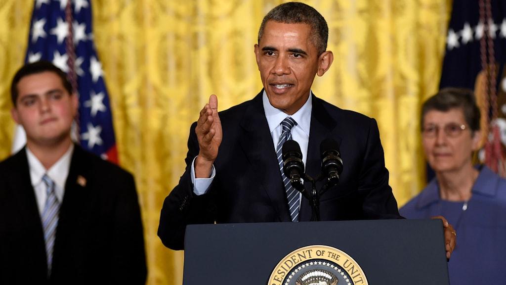 Barack Obama talar från podiet i Vita huset, omgiven av medarbetare