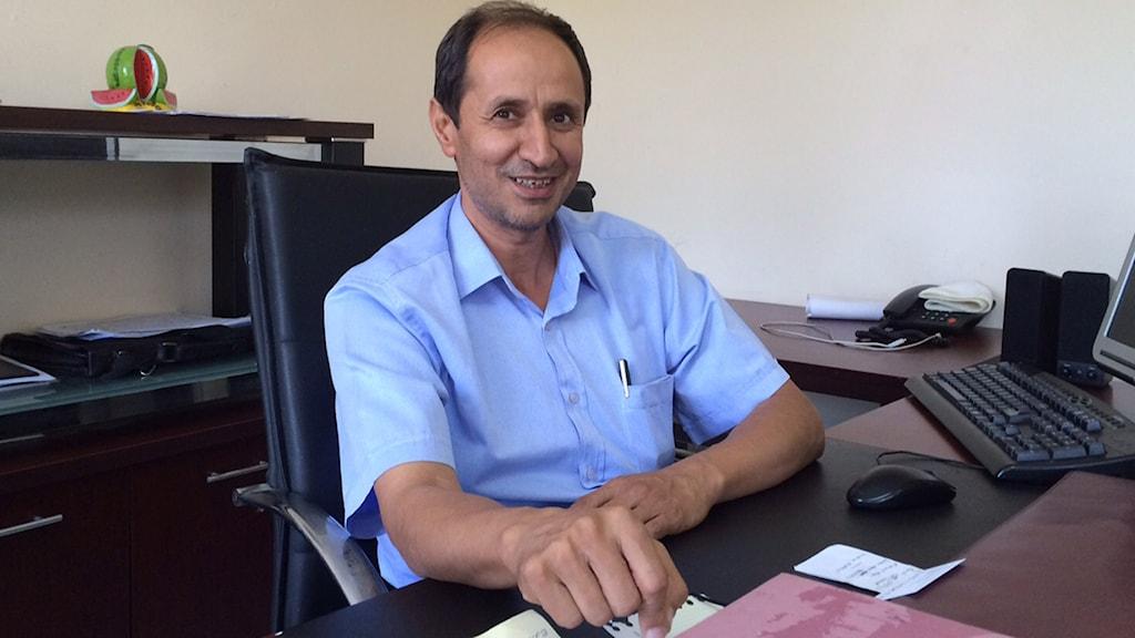 Man i blå skjorta sitter vid skrivbord