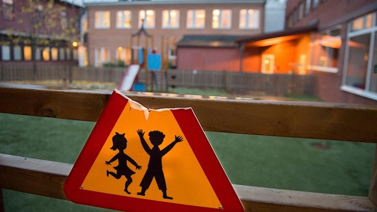 Trasig skylt med lekande barn utanför tegelbyggnad