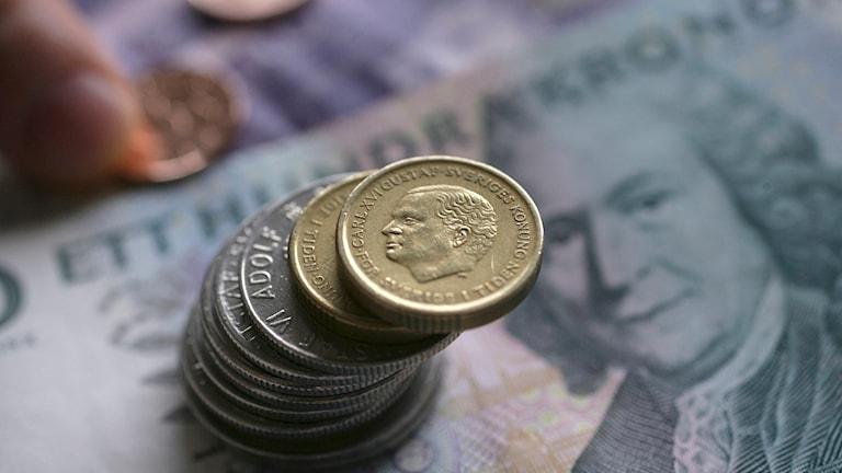 Svenska pengar, en stapel med mynt ovanpå en svensk 100-kronorssedel. Foto Fredrik Sandberg/TT.
