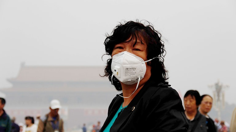 Kinesisk kvinna iförd munskydd i Peking i samband med tung smog. Foto: Ga la/TT.