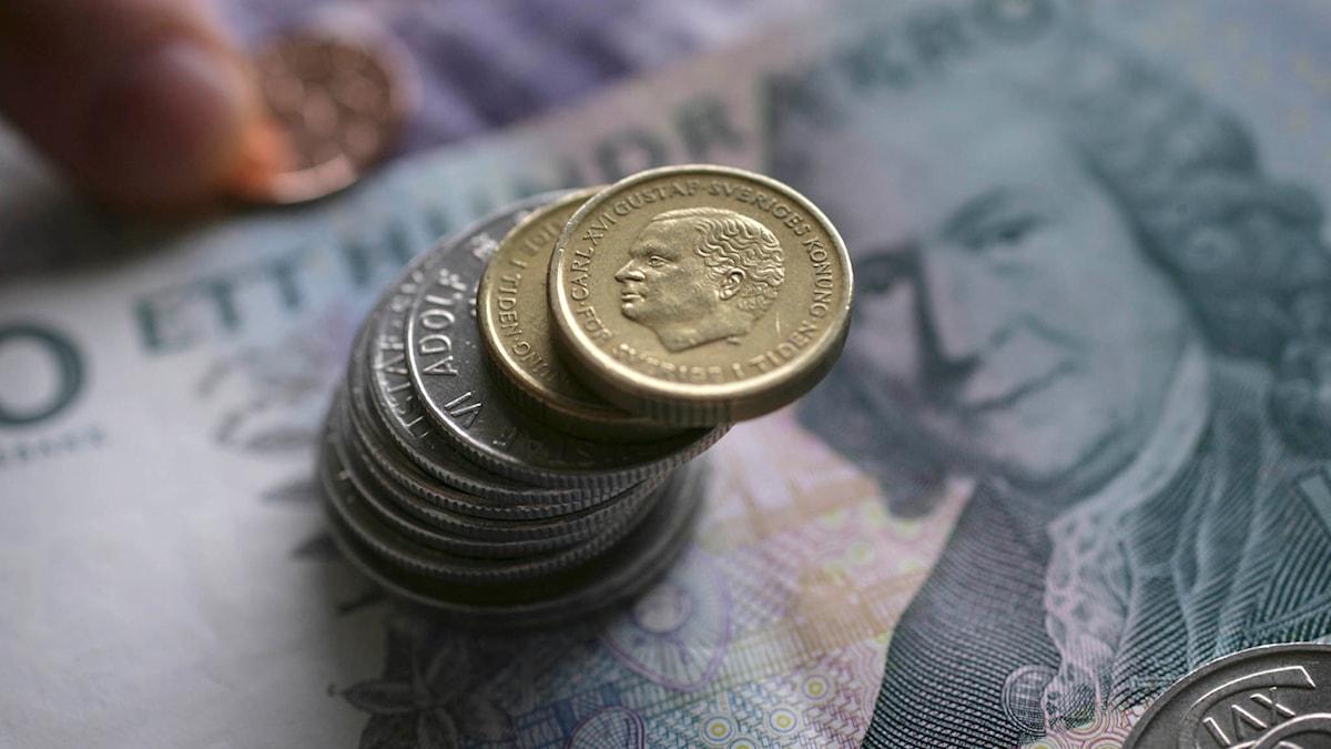 Svenska pengar. Mynt staplade ovanpå en hundralapp. Foto: Fredrik Sandberg/TT.